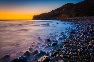 Long exposure of waves crashing on rocks at sunset, taken at Pelican Cove, in Rancho Palos Verdes, California.